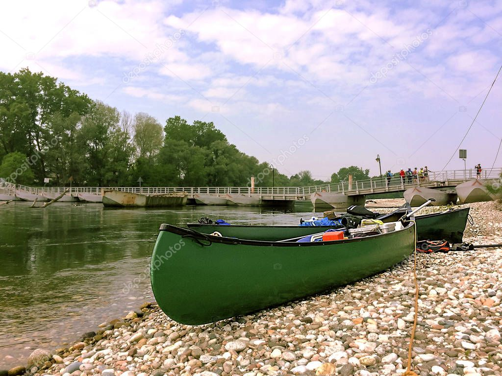 Green canoe waiting to enter the river during springtime