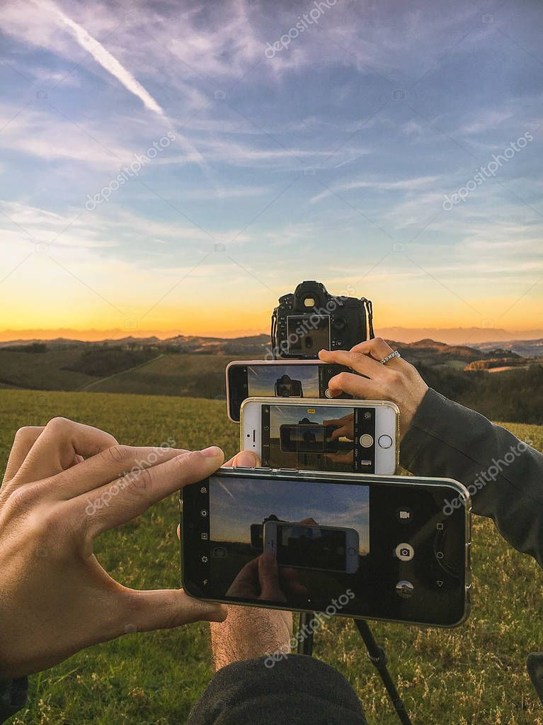 Photographing landscape at sunset with smartphones and reflex cameras