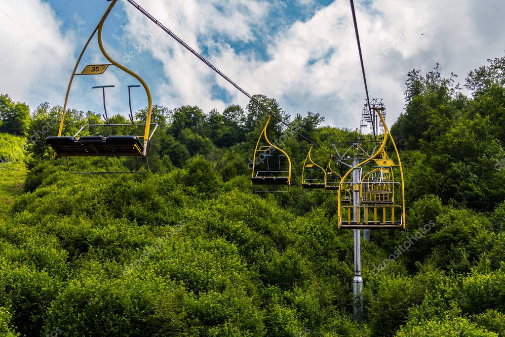 Cable car with cabins for three seats and yellow railings against the backdrop of lush green trees
