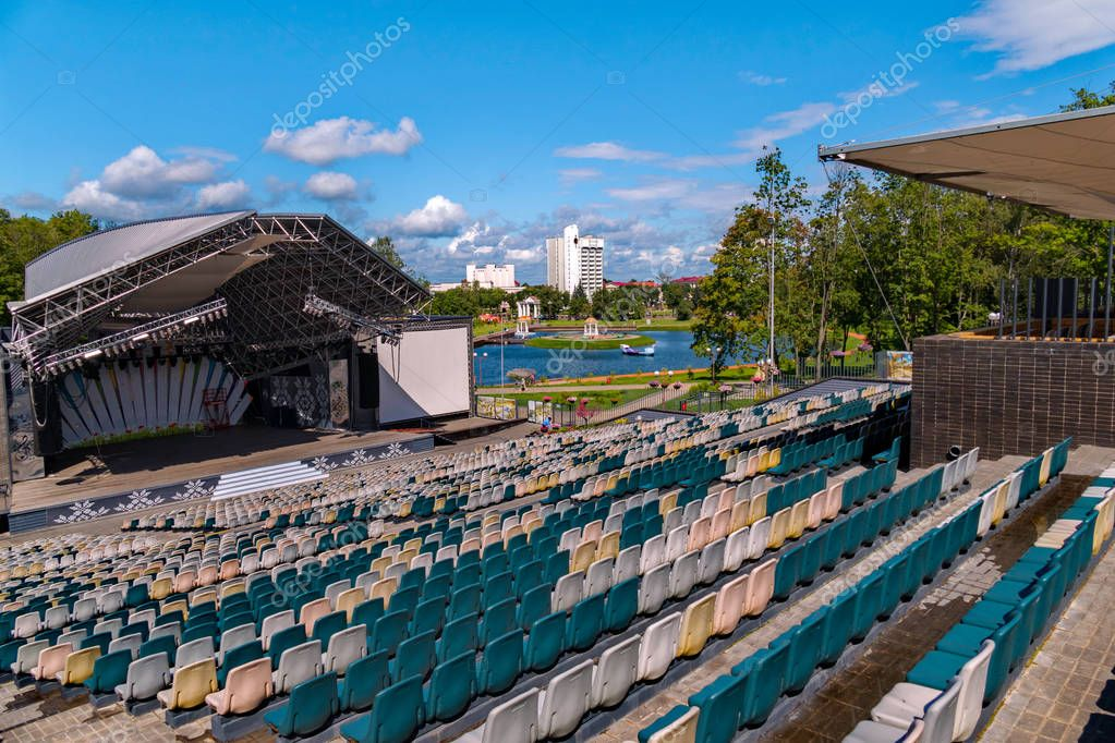 Summer concert hall with empty stands in the open air against the background of a green park zone with a lake