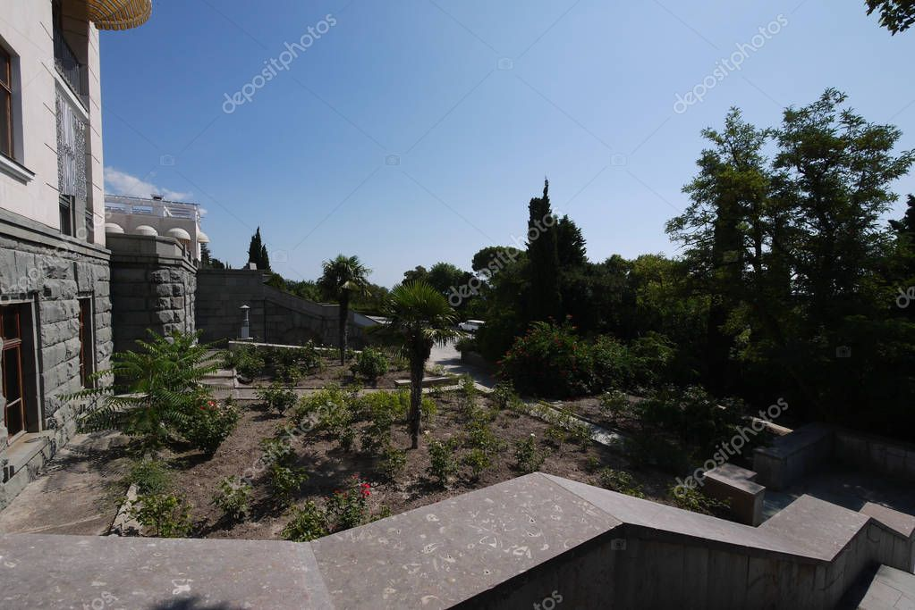 view from the granite steps of the stairs to the park with palm trees growing in the flower bed and blue cloudless sky