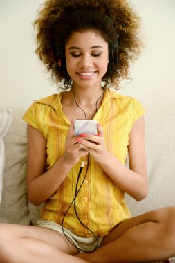 beautiful smiling girl listen music with earbud at home