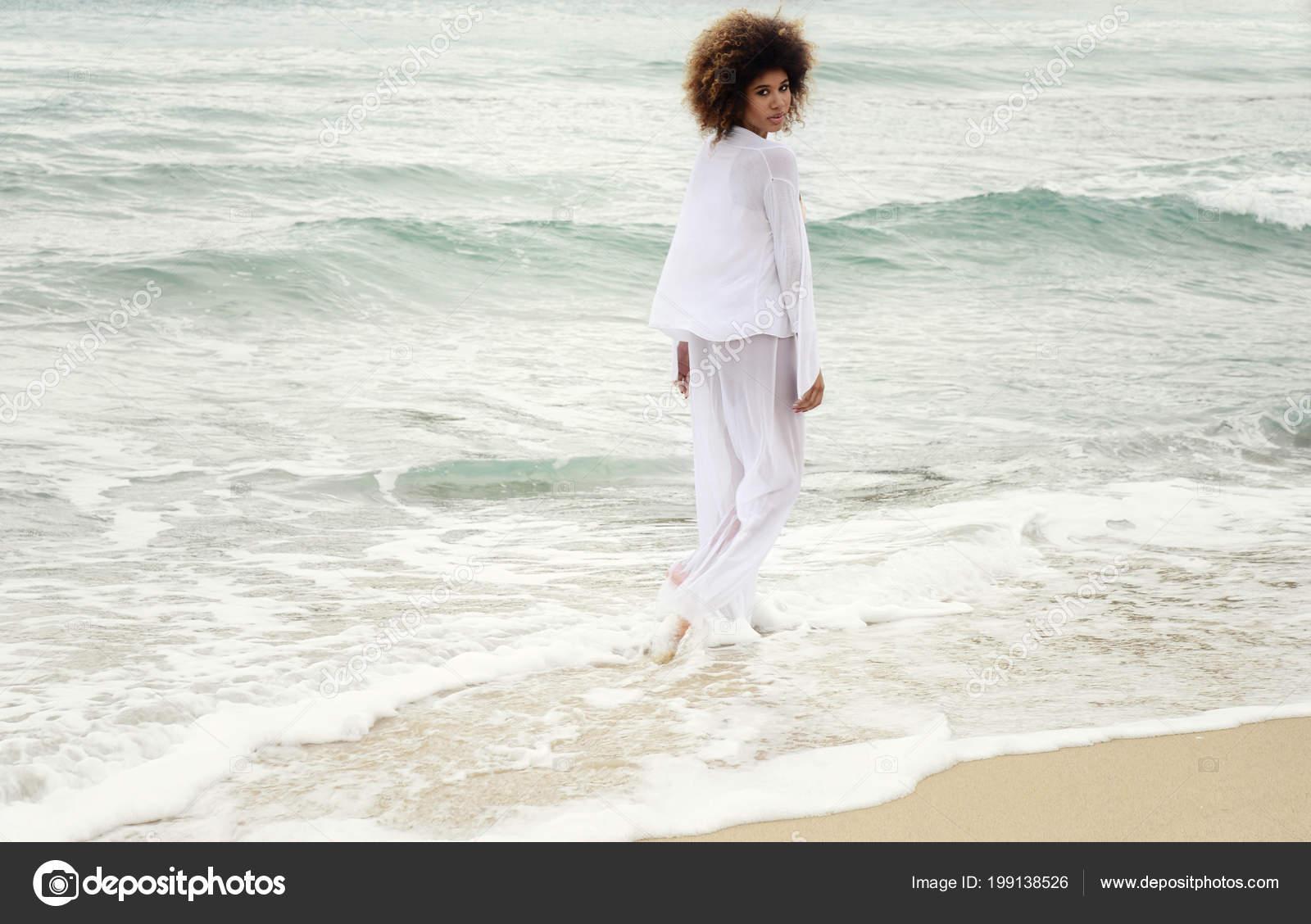 059d7ee82987 Bella ragazza con capelli afro e vestito bianco camminare in riva al mare —  Foto di claudio.gangi.fastwebnet.it