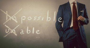 positive thinking concept handwritten on black chalkboard with businessman