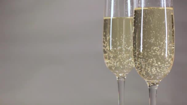 Champagne bubliny ve sklenici na šedém pozadí