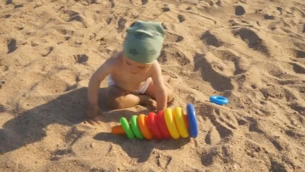 A little boy is playing on the sand on the beach. A baby crawls and laughs studying all around.