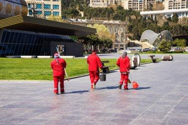 Şehir parkında kırmızı tulumlu sokak temizleyicileri.