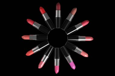 Lipsticks of different colors arranged in a circle on black background. 3d illustration.