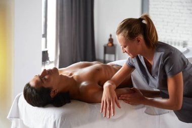 Professional masseuse doing arm massage with forearms and cubits for male client. Young man relaxing receiving body massage at the spa center. Relaxation therapy resort recreation.