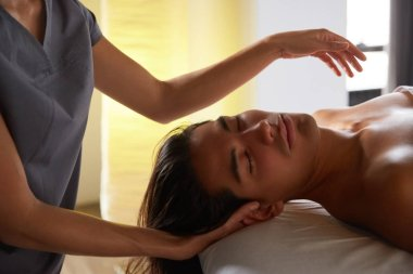 Close up shot of a professional masseuse doing face and head massage for her male client. Handsome young man relaxing receiving facial massage at the spa center. Relaxation therapy resort recreation.