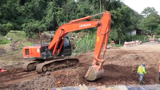 Chiangrai / Thajsko - 20. srpna 2018, Hitachi oranžový bagr pracuje na silnici v lese, Chiangrai - Chiangmai silnice 118