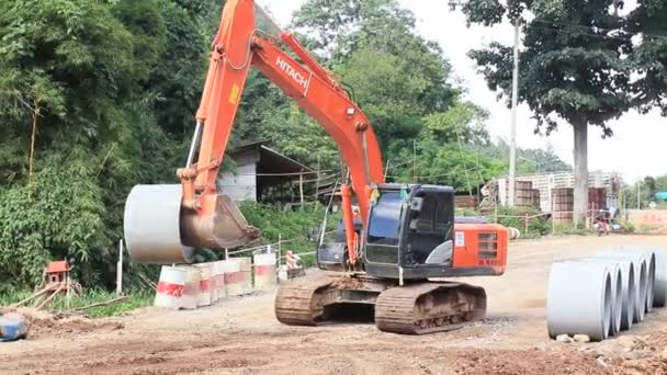 Chiangrai / Thailand - August 20, 2018, the Hitachi orange excavator works on the road in the forest, moving the concrete ring, Chiangrai - Chiangmai road 118