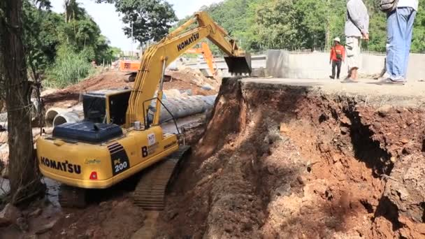 Chiang Rai / Thailand - August 20, 2018, rehabilitation of roads after flooding. A yellow excavator is working in the river. Workers and concrete pipes. Chiang Rai - Chiang Mai road 118
