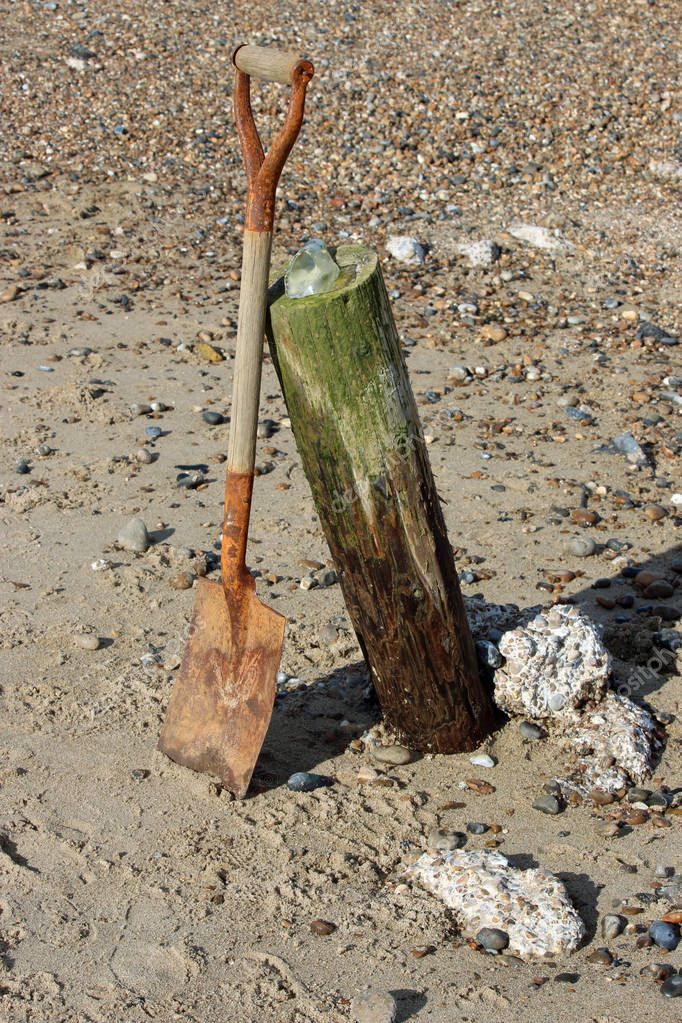 Old wooden handled spade leaning against a half buried breakwater on a beach. Surrounded by sand, shingle and lumps of concrete. Small piece of seaglass on top of the breakwater.
