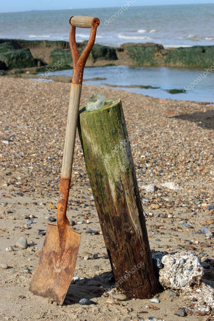 Old wooden handled spade leaning against a half buried breakwater on a beach. Surrounded by sand, shingle and lumps of concrete. Small piece of seaglass on top of the breakwater. Sea and blue sky in the background.