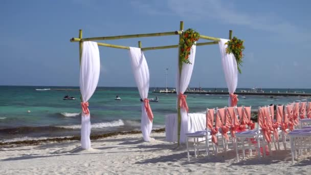 Wedding arch decorated with flowers and large wind-developing fabrics on tropical beach. Turquoise water of the Caribbean Sea. Riviera Maya Mexico