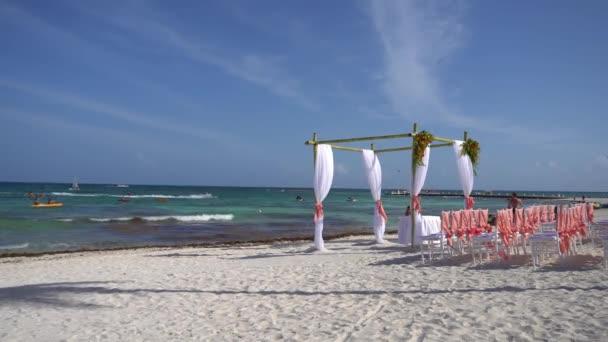 Svatební oblouk zdobí květinami a velkým větrem rozvoj tkaniny na tropické pláži. Tyrkysové vody Karibského moře. Riviera Maya Mexiko