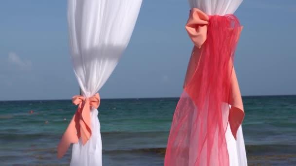 Svatební oblouk zařízené s velkým větrem rozvoj tkaniny na tropické pláži. Tyrkysové vody Karibského moře. Riviera Maya Mexiko