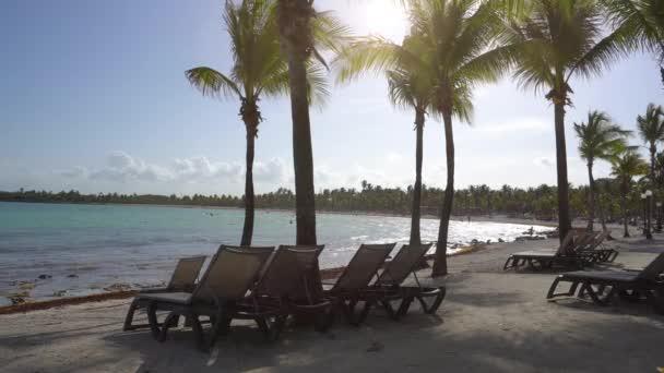 Pohled na pláž Hotelový resort Luxusní tropické pobřeží. Listy kokosových palem vlající ve větru proti modré obloze. Tyrkysové vody Karibského moře. Riviera Maya Mexiko