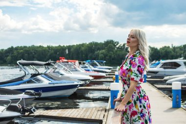 Beautiful girl in a dress is stand on the pier against the backdrop of yachts in summer.