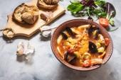 Fotografie Französische Fischsuppe Bouillabaisse mit Lachsfilet, Garnelen, Meeresfrüchte, Muscheln auf konkreten Hintergrund. Leckeres Abendessen