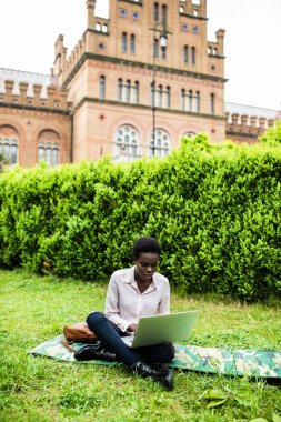 Young female african american woman enjoying a sunny day at the park, working on computer. Student.