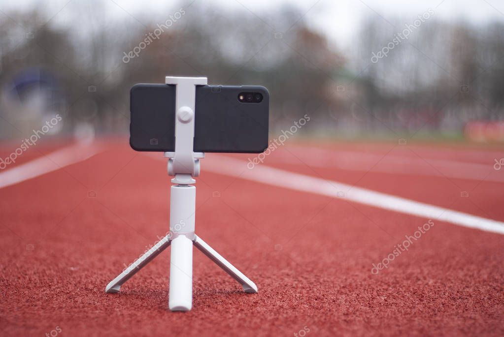 Mock up of a black smartphone with a tripod. White screen for design template on the background of the red track for running and sports stadium.