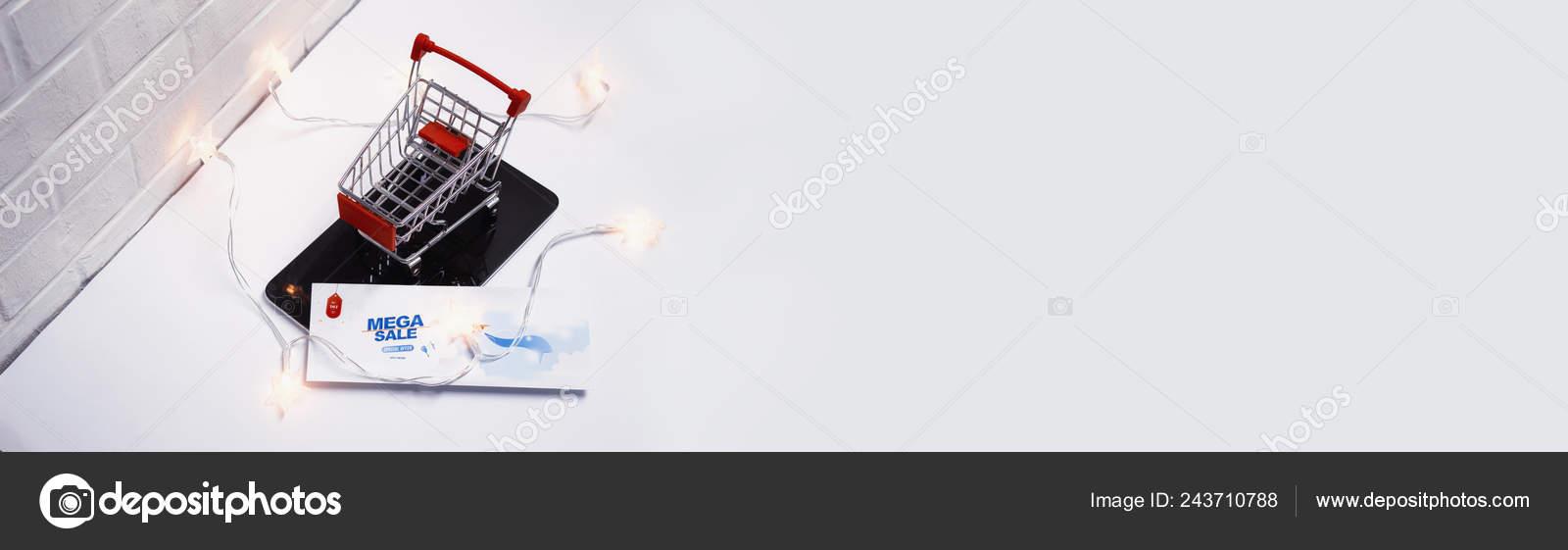 3a9535b33 Concepto de venta online. Carrito de la compra y el volante con luces que  brillan intensamente en la tableta y en el fondo de una pared de ladrillo–  Imagen ...