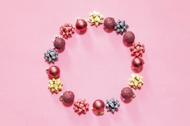 Christmas ornaments forming a circle with a pink background
