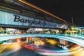 Bangkok, Thaiföld - 2017. november 25.: jelzőlámpa trail a főút elágazás közelében Mbk bevásárlóközpont, Bangkok, Thaiföld. Turisztikai reklám logó a Bts sky vonat pályán, pedestrain sétál a skywalk terület
