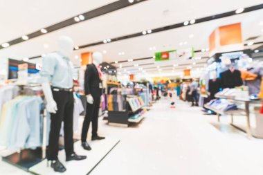 Blurred, defocused background of men's clothing shops in modern shopping mall or department store. Shopaholic lifestyle, or fashion outlet business concept