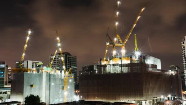 Časosběr z rozestavěné staveniště v noci ve městě nebo centrální obchodní čtvrti. Pokročilé techniky budov nebo průmyslové země konceptu