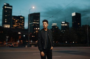Portrait of stylish man on night city background pose to camera