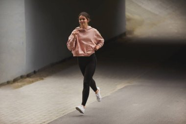 Sporty girl run on the street with night city baclkground