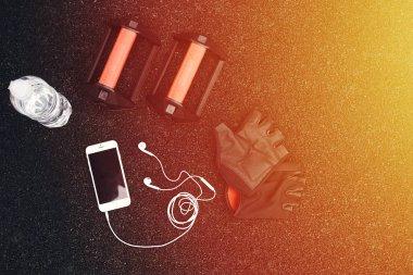 Set of water, phone, gloves, headphones on black background