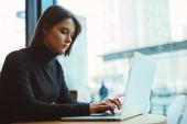 Frau schaut sich um und lächelt während der Arbeit im Café auf ihrem Laptop. Porträt einer stilvoll lächelnden Frau in Winterkleidung bei der Arbeit am Laptop. weiblicher Businessstil mit Sonne. - Bild