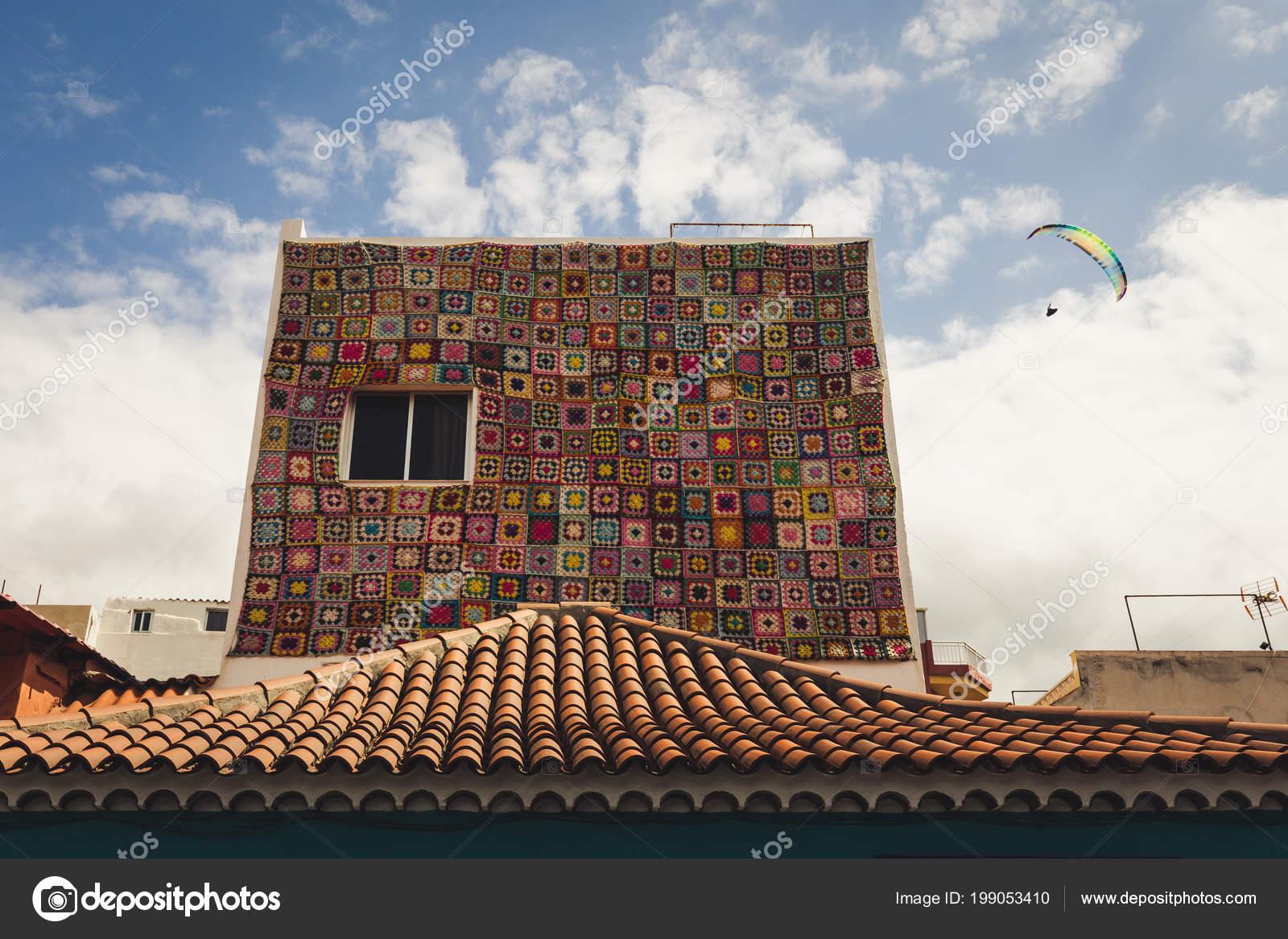 Gevel van het huis versierd met kleurrijke tapijt vliegende