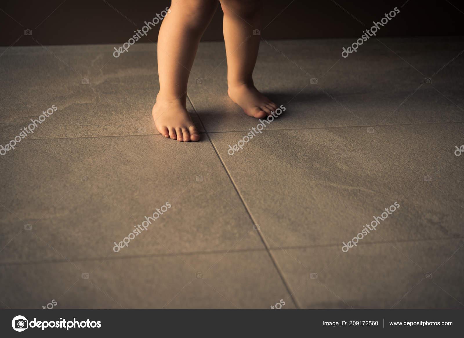 Bambino piedi nudi sono stare riscaldamento pavimento piastrelle