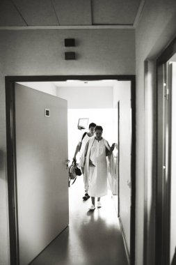Pregnant woman and her husband leave the hospital rooml. The woman has a scramble and it hurts her
