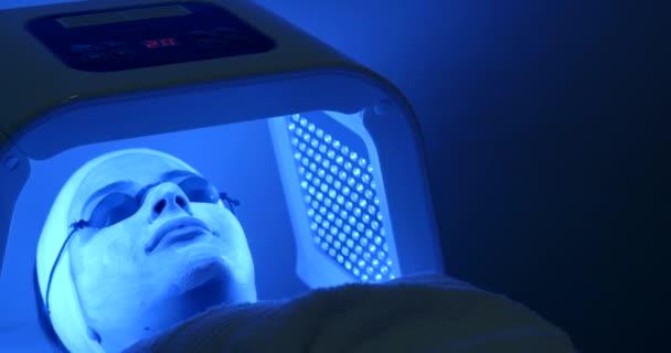 Kosmetika a ošetření obličeje. LED světelná terapie pro ženy s maskou a brýle v profesionálním salónu. Boční pohled. 4 k video