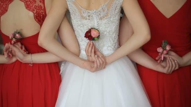 Zadní pohled na nevěstu a dvě družičky v červených šatech drží krásné boutonnieres růžových růží. Bez tváře. Svatební přípravy