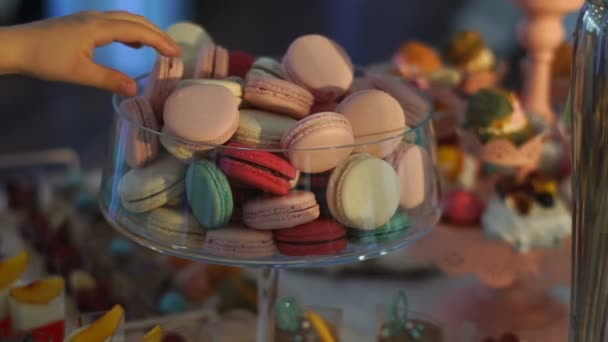 The dessert stand is full of macarons of different colours at the wedding table. The female hand is taking one of cookies.