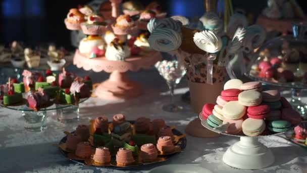Wedding candy buffet. Dessert bar covered with different colorful and delicious cakes, cake-pops, cookies and macarons decorated with fruits.
