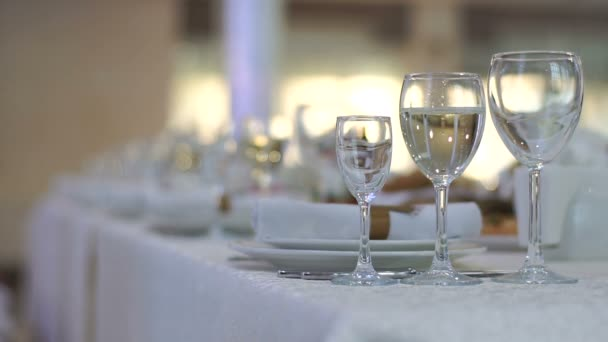 Wedding table set in white colors. Close-up view of three glasses. Moving bubbles in the glass. No people.