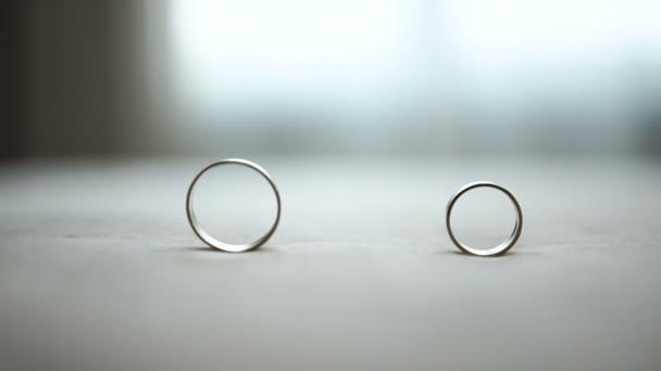 Složení dvou svatební prsteny u stolu. Mužský kruh se navíjí do jiného.