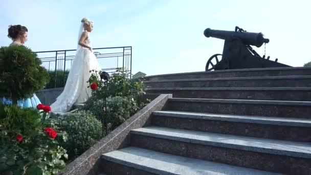 Okouzlující nevěsta blondýnka a její dvě družičky v modré šaty jdou nahoru venkovní schody