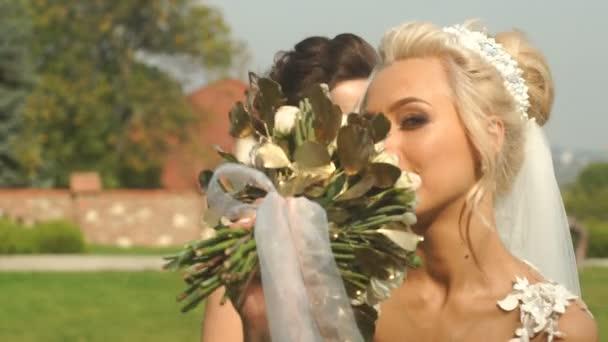 Šťastné krásné blonde nevěsta s okouzlující úsměv a svatební kytice je pózovat s její družičky v zahradě