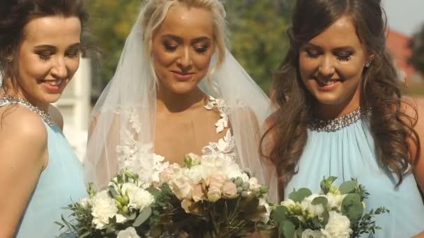 Atraktivní blondýna nevěsta a její krásné družičky jsou vonící svatební kytice a šťastně hovořit venkovní