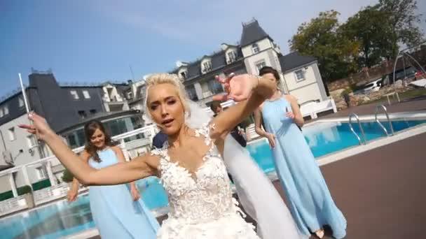 A bájos menyasszony és a vőlegény és a koszorúslányok és a legjobb férfi, boldogan táncol a medence melletti érzelmi felvétel.