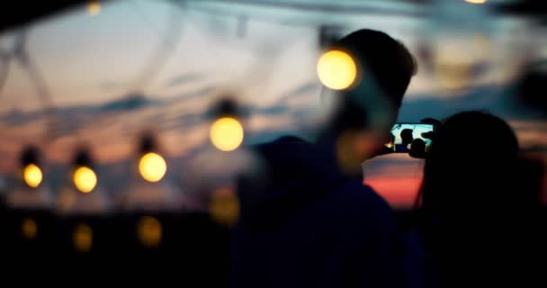 Back view of silhouettes of two lovers looking at their selfie and tenderly kissing while standing in front of the string of lamps during the sunset.